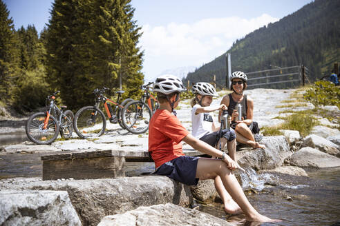 Mother and her children having a break at a mountain stream during a bicycle tour - FKF03538