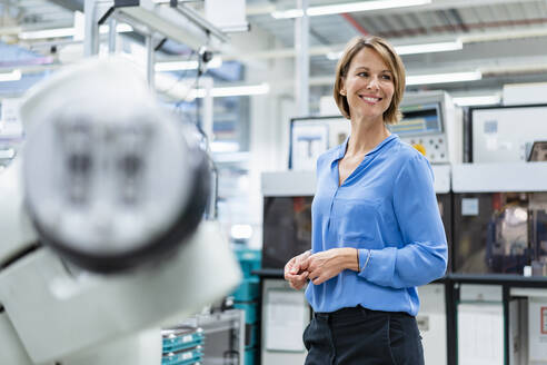Portrait of businesswoman at assembly robot in a factory - DIGF07813