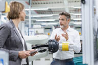 Businesswoman and man talking at assembly robot in a factory - DIGF07825