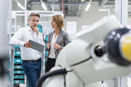 Businesswoman and man with tablet talking at assembly robot in a factory - DIGF07834