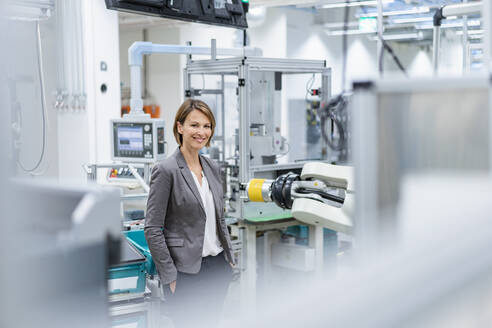 Portrait of a smiling businesswoman in a modern factory - DIGF07840