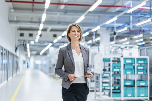 Smiling businesswoman with tablet in a modern factory - DIGF07852