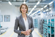 Portrait of a confident businesswoman in a modern factory - DIGF07867