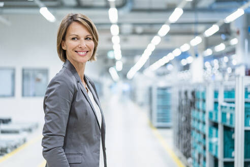 Portrait of a smiling businesswoman in a modern factory - DIGF07870