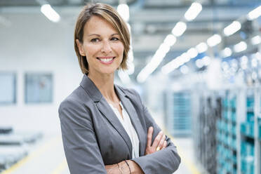 Portrait of a smiling businesswoman in a modern factory - DIGF07873