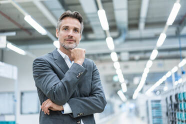Portrait of a confident businessman in a modern factory - DIGF07876
