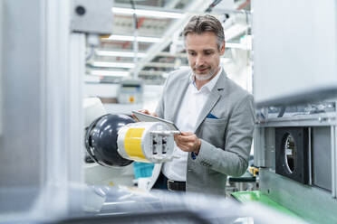 Businessman with tablet at assembly robot in a factory - DIGF07879