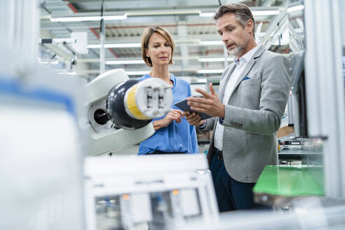 Businessman with tablet and woman talking at assembly robot in a factory - DIGF07882