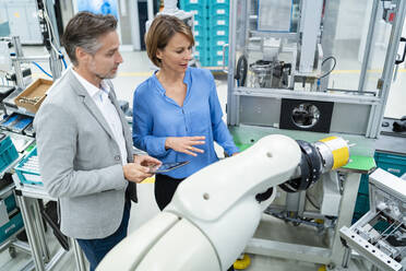 Businessman with tablet and woman talking at assembly robot in a factory - DIGF07885