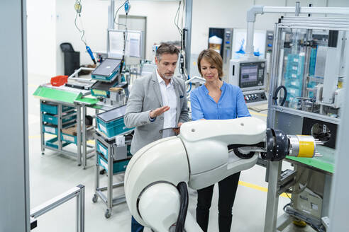 Businessman with tablet and woman talking at assembly robot in a factory - DIGF07888