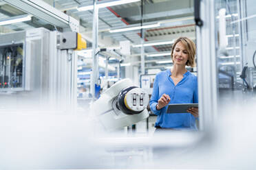 Businesswoman with tablet at assembly robot in a factory - DIGF07891