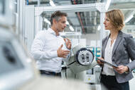 Businesswoman and man talking at assembly robot in a factory - DIGF07894
