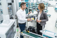 Businesswoman and man talking at assembly robot in a factory - DIGF07897