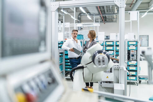 Businesswoman and manwith tablet talking in a modern factory - DIGF07900