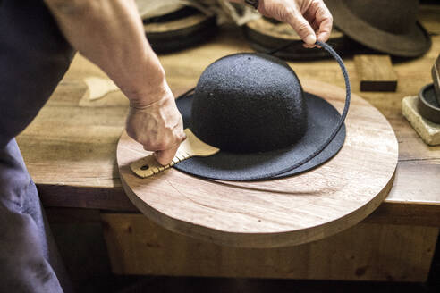 Midsection of man making hat on table in workshop - DAWF00941