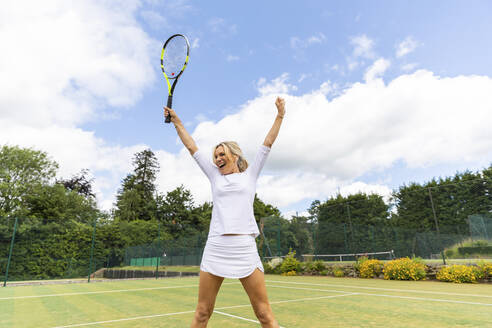 Happy female tennis player celebrating the victory on grass court - WPEF01772