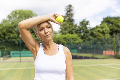 Tired female tennis player taking a break on grass court at tennis club - WPEF01778
