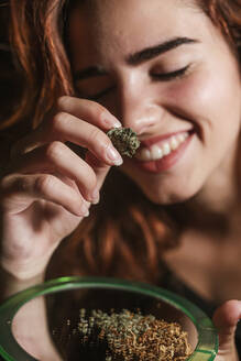 Smiling young woman with marihuana at home - LJF00645