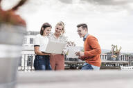 Casual business people with laptop meeting on roof terrace - UUF18548