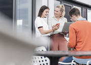 Casual business people with smartphone and laptop meeting on roof terrace - UUF18551