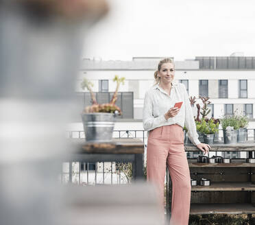 Portrait of casual businesswoman with cell phone on roof terrace - UUF18554