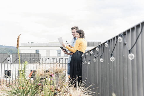 Casual businessman and woman with laptop and documents meeting on roof terrace - UUF18557