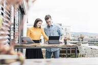 Casual businessman and woman with documents and tablet meeting on roof terrace - UUF18560