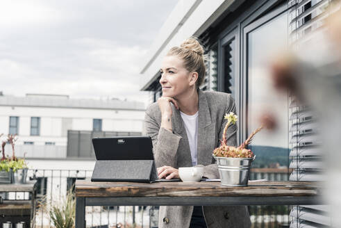 Businesswoman with tablet on roof terrace having a break - UUF18569