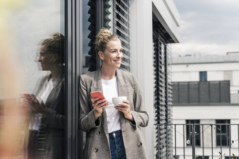 Smiling businesswoman with cell phone and coffee cup standing on roof terrace - UUF18575