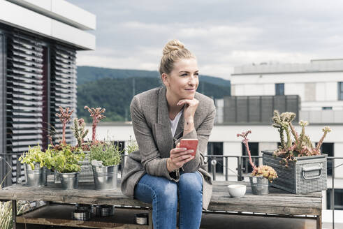 Businesswoman with cell phone sitting on roof terrace having a break - UUF18578