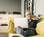 Casual businesswoman using laptop on couch in office lounge - UUF18587