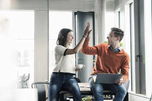 Happy casual businessman and woman high fiving in office - UUF18599