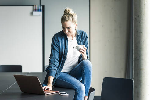 Businesswoman with cup of coffee sitting on table in office using laptop - UUF18617