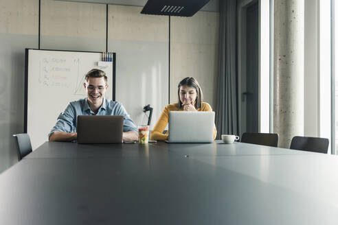 Happy businessman and businesswoman with laptops in conference room - UUF18623