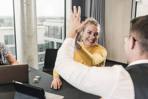Happy businessman and woman high fiving in office - UUF18647