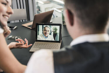 Colleagues having a video conference in conference room - UUF18650