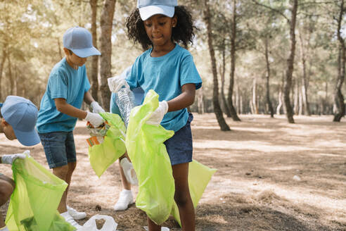 Group of volunteering children collecting garbage in a park - JCMF00108