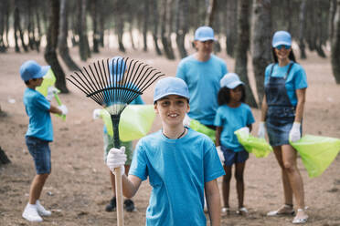 Portrait of a boy with group of people collecting garbage in a park - JCMF00114