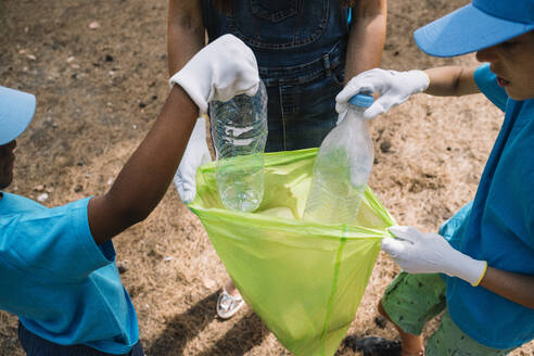 Close-up of volunteering children collecting garbage in a park - JCMF00117
