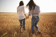 Caucasian women holding hands in rural field - BLEF13910