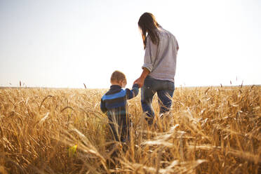 Caucasian mother and son walking in rural field - BLEF13913