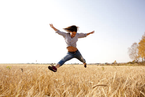 Caucasian woman jumping for joy in rural field - BLEF13925