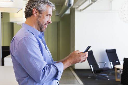 Caucasian businessman using cell phone in office - BLEF14006