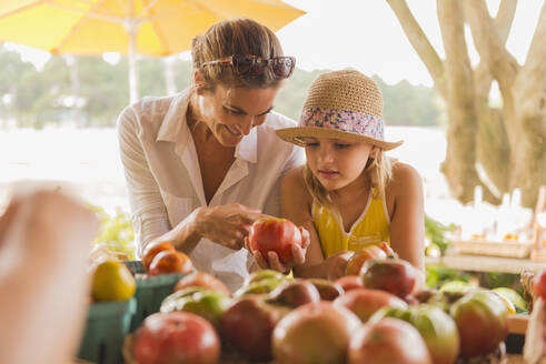 Mixed race mother and daughter browsing produce at farmers market - BLEF14084