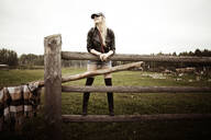 Caucasian woman standing on wooden fence at ranch - BLEF14147