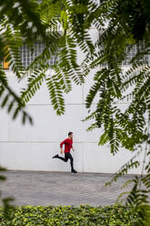 Young athlete doing intensive running training in the city - MAUF02727