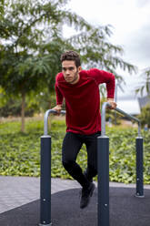 Athlete training on bars in the city - MAUF02730