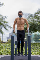 Athlete training on bars in the city, wearing breathing mask - MAUF02733