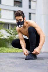 Young athlete tying shoes, wearing breathing mask - MAUF02736