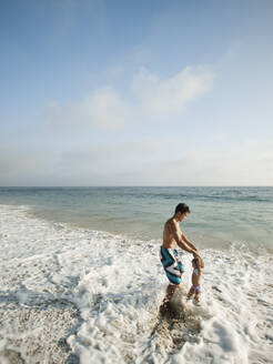 Mixed race father and daughter playing in ocean together - BLEF14262